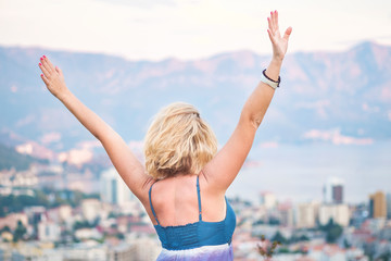 Portrait from the back - a young blonde girl stands on the viewing platform and looks at the city, the seacoast and the mountains, arms outstretched. Concept of freedom and happiness