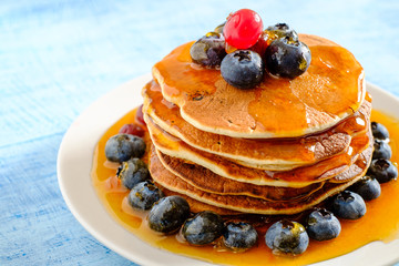 Stack of pancakes with fresh blueberries and maple syrup