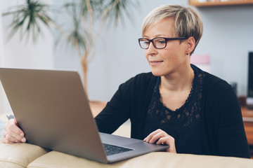 Middle-aged woman in glasses working on a laptop