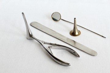Medical instruments for examining the ear, throat, nose on white gauze background. Medical spatula, ear funnel, nasal Venna mirror, guttural mirror. Retro. Black and white photo.