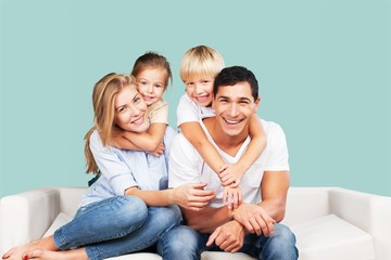 Beautiful smiling family sitting at sofa at