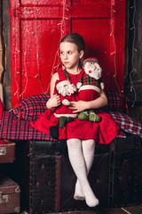 A girl in a red dress sits on old suitcases and holds toy Santa and an elf in her hands.
