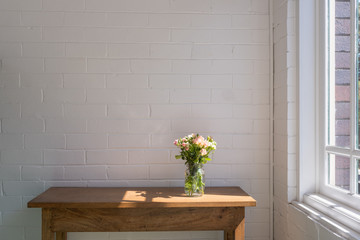 Small pink and cream roses in glass jar on wooden oak sidetable against white painted brick wall next to window with afternoon sunlight