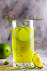 Delicious yellow drink with a handful of green lemon. Cocktail with limnom concrete background. Yellow cocktail with lemon.