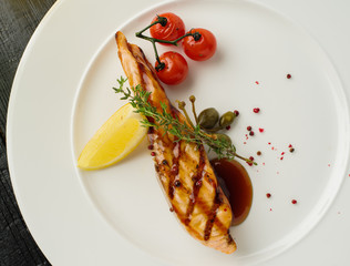 Grilled salmon steak with lemon and cherry tomatoes. View from above