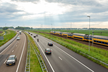 Cars on the A44 highway and a train near Abbenes.