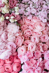 Beautiful blossoming flower bed of freshly delivered flowers at the florist shop: peonies, roses, ranunculus, tulips, carnations,eustoma lisianthks, hydrangea in tender pink colours, top view