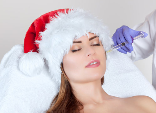 The cosmetologist makes the Botulinum toxin injection on the face skin of a beautiful, young woman in the Santa Claus hat. New Year's and Cosmetology concept.