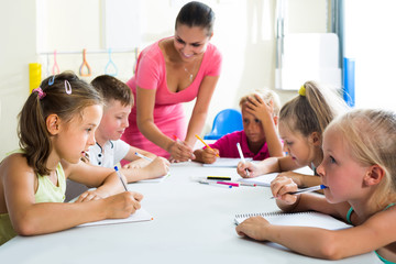 children making writing exercises with help of teacher in class