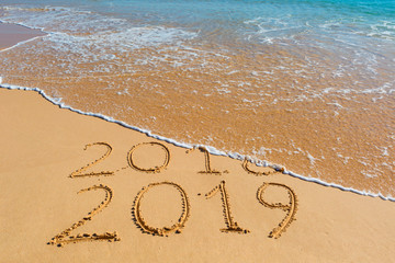 2018 2019 inscription written in the wet yellow beach sand being washed with sea water wave