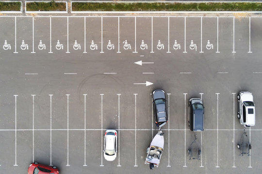 Almost empty outdoor car parking with handicapped symbol icon. Prking places reserved for disabled person. Aerial drone view