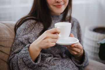 Happy smiling young woman enjoy morning coffee, close up. Comfort, home, joy, cosiness concept