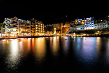 Colorful light reflections.  Seaside resort town of Xlendi at night.  This town right off the Mediterranean Sea is located on the island of Gozo, Malta.
