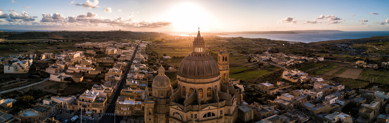 Aerial drone sunrise photo - Rotunda St. John Baptist Church in the town of Xewkija, Gozo.  Country of Malta.  Mediterranean Sea on the horizon Wall mural