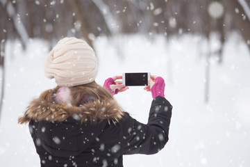 Rear view of girl on snow day holding blank screen smartphone. Holiday concept