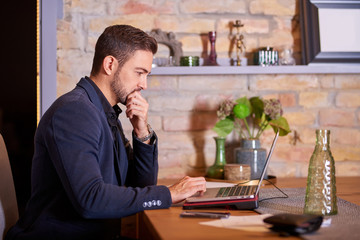 A handsome young businessman using a laptop and thinking in office environment.