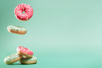 Donuts with pink and green icing with sprinkles on mint backround with copyspace for your text