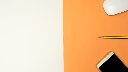 Wall Mural - smartphone,pencil  on white and orange background business concept