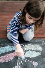 Young girl sitting and drawing a butterfly on a chalkboard