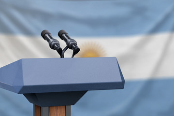 Podium lectern with two microphones and Argentina flag in background