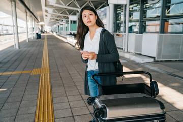 asian traveler using smart phone contacting