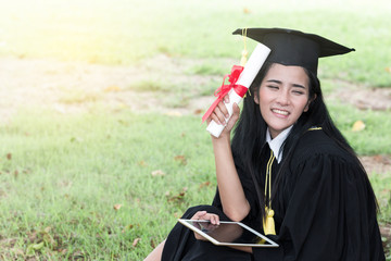 Happy graduate young Asian woman in cap and gown holding a certificated in hand, A diploma with red ribbon education concept in garden