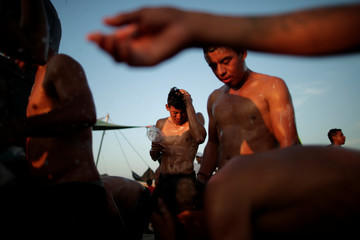 Migrants men, part of a caravan of thousands traveling from Central America en route to the United States, take a shower at a makeshift camp in Juchitan