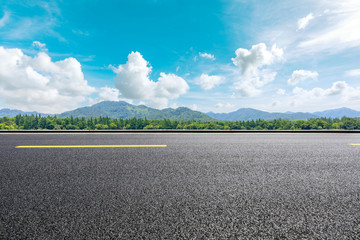 Asphalt road and beautiful mountain under the blue sky