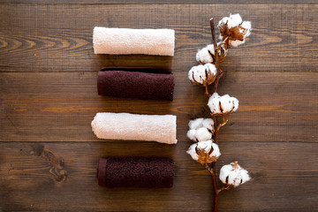 Cotton towels high quality. Set of towels twisted coil near dry cotton flowers on dark wooden background top view copy space