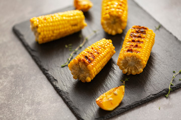 Grilled corn grilled on fire. On a dark stone table.