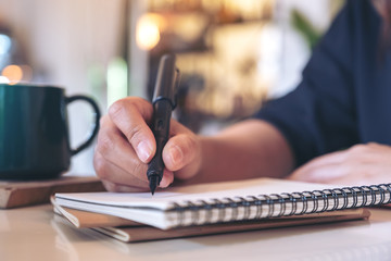 Closeup image of a woman's hand writing on blank notebook with coffee cup on table in cafe