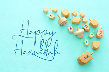 Image of jewish holiday Hanukkah with wooden dreidels colection (spinning top) over mint background.
