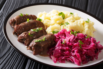 Beef Rouladen with gravy on a plate served with mashed potatoes and red cabbage close-up. horizontal