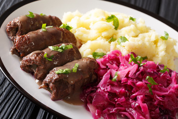 Beef Rouladen or Rinderrouladen German classic dish served with mashed potato and red cabbage close-up. horizontal