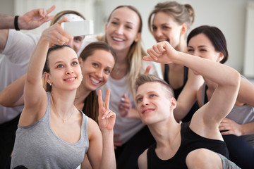 Group millennial positive laughing sportive athletic girls and guys at gym training studio. People smiling make peace sign symbol taking selfie photo feels happy and satisfied friendship unity concept