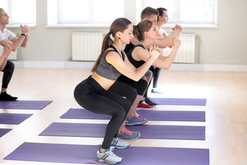 Group of millennial sportive athletic people workout together at gym doing squat exercise standing on violet rubber carpets mats. Girls and guys performing crouching, work on buttocks and hips muscles