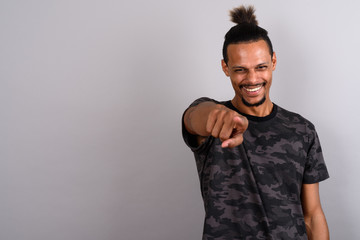 Young bearded handsome African man against gray background