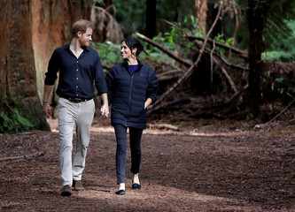 Britain's Prince Harry and Meghan, Duchess of Sussex walk through a Redwoods forest in Rotorua, New Zealand, Wednesday