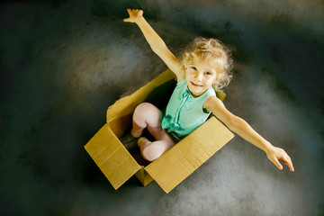 The little blonde smiles inside a cardboard box. shows us hands. dark background. toning