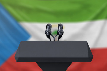 Podium lectern with two microphones and Equatorial Guinea flag in background