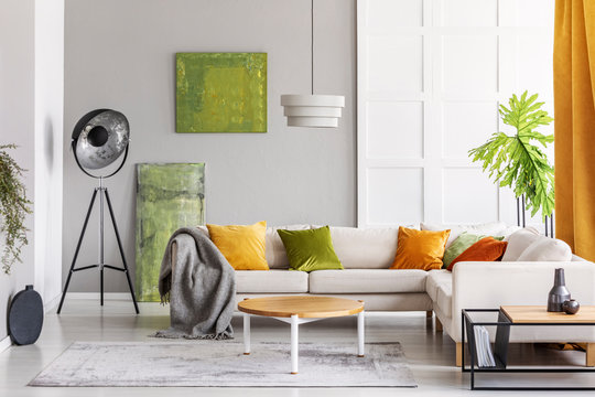 Paintings on the wall and industrial lamp in the corner of elegant living room interior with golden lime accents, real photo with copy space