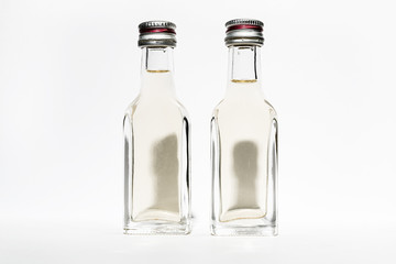 Two bottles of vintage alcohol with shadows in the shape of the heads of two young men.