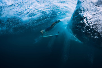 Professional surfer with surfboard dive underwater with big ocean wave.