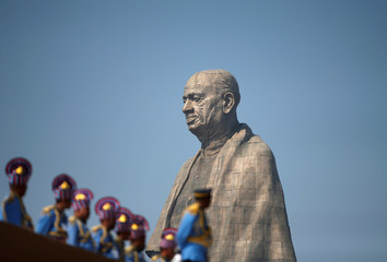 """Police officers stand near the """"Statue of Unity"""" portraying Sardar Vallabhbhai Patel, one of the founding fathers of India, during its inauguration in Kevadia"""