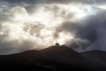 Photographer takes pictures on the top of a mountain with dramatic rainy clouds around