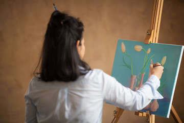 Female artist working in front of  canvas and painting at art studio.