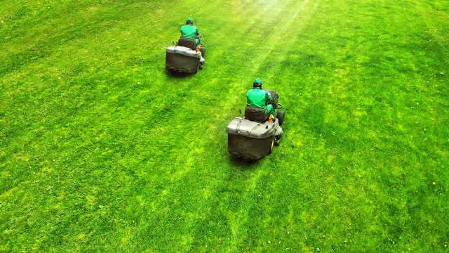 Aerial. Pair of lawn mowers on a grass. Professional gardening background with a two workers and two lawnmowers.