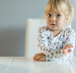 Little blonde toddler girl sitting at kitchen table and looking at camera