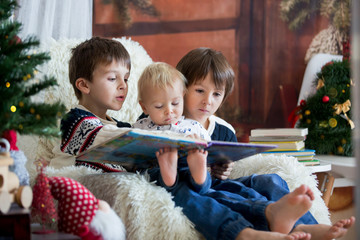 Three children, boy brothers, sitting in rocking chair in cozy living room with christmas decoration, reading a book