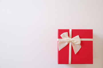 Close-up  red gift box with white ribbon on white background.
